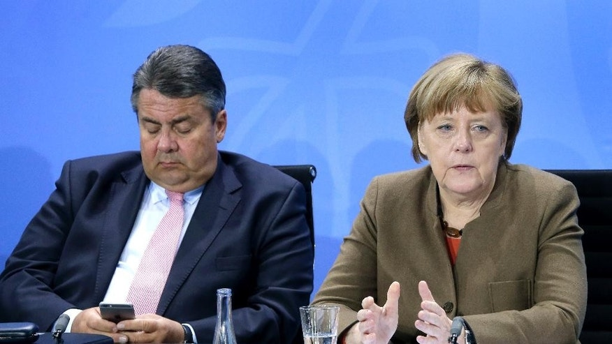 Sigmar Gabriel, left, Chairman of the German Social Democrats, looks at his smartphone as German Chancellor Angela Merkel, right, speaks during a press conference in Berlin, Germany, Thursday, April 14, 2016 on the results of a meeting of the heads of the German government coalition. (AP Photo/Michael Sohn)
