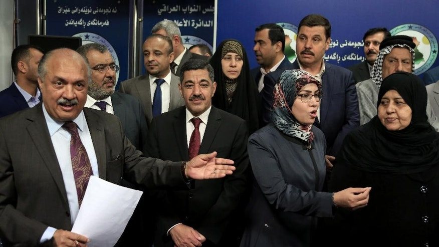 Lawmakers who held a sit-in overnight inside the parliament building gather during a news conference, in Baghdad, Iraq, Wednesday, April 13, 2016. For the second consecutive day, at least one hundred lawmakers from Shiite and Sunnis, have continued holding a sit-in inside the hall of meetings of the parliament, protesting at the postponement of vote on the technocrat cabinet. (AP Photo/Karim Kadim)