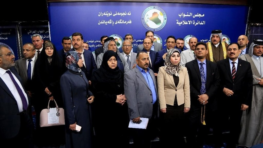 Members of parliament, who held a sit-in overnight inside the parliament building, stand during a news conference, in Baghdad, Iraq, Wednesday, April 13, 2016. For the second consecutive day, at least one hundred lawmakers from Shiite and Sunnis, have continued holding a sit-in inside the hall of meetings of the parliament, protesting at the postponement of vote on the technocrat cabinet. (AP Photo/Karim Kadim)
