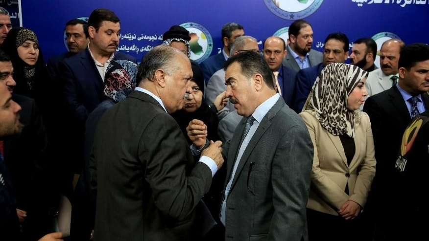 Members of parliament, who held a sit-in overnight inside the parliament building, gather during a news conference, in Baghdad, Iraq, Wednesday, April 13, 2016. For the second consecutive day, at least one hundred lawmakers from Shiite and Sunnis, have continued holding a sit-in inside the hall of meetings of the parliament, protesting at the postponement of vote on the technocrat cabinet. (AP Photo/Karim Kadim)