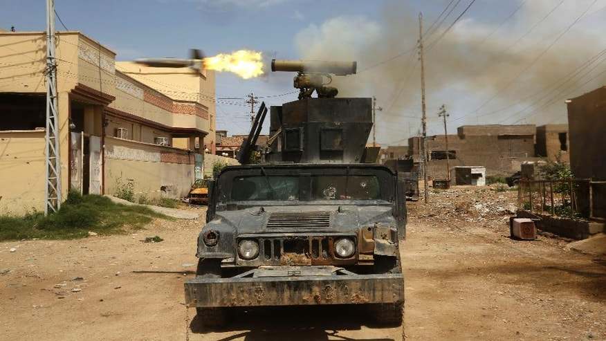 Iraq's elite counterterrorism forces fire towards extremist positions during fights between Iraqi security forces and Islamic State group during a military operation to regain control of Hit, 85 miles (140 kilometers) west of Baghdad, Iraq, Wednesday, April 13, 2016. (AP Photo/Khalid Mohammed)