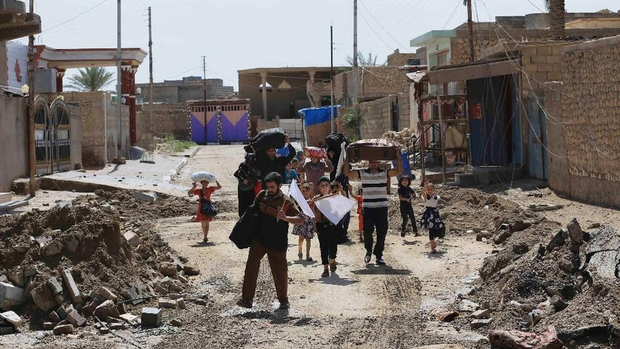 People flee their homes during fighting between Iraqi security forces and the Islamic State group during a military operation to regain control of Hit, 85 miles (140 kilometers) west of Baghdad, Iraq, Wednesday, April 13, 2016. (AP Photo/Khalid Mohammed)