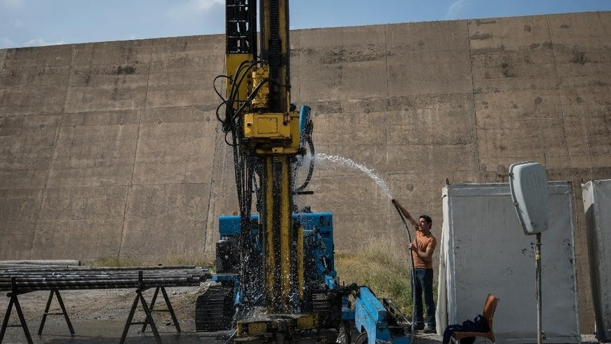 A worker sprays water on machinery used in the maintenance at the Mosul Dam in northern Iraq on Thursday, April 14, 2016. A team of Italian specialists arrived Thursday at the site of the Mosul Dam as part of an emergency campaign to repair Iraq's largest dam before it collapses.(AP Photo/Alice Martins)