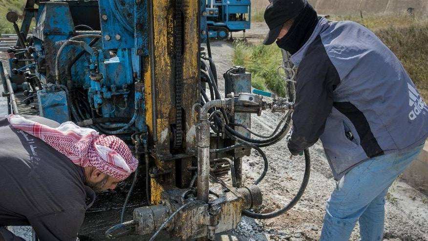 Workers adjust pipes and hoses that is used for pumping concrete into the ground at Mosul Dam in northern Iraq on Thursday, April 14, 2016. A team of Italian specialists arrived Thursday at the site of the Mosul Dam as part of an emergency campaign to repair Iraq's largest dam before it collapses.(AP Photo/Alice Martins)