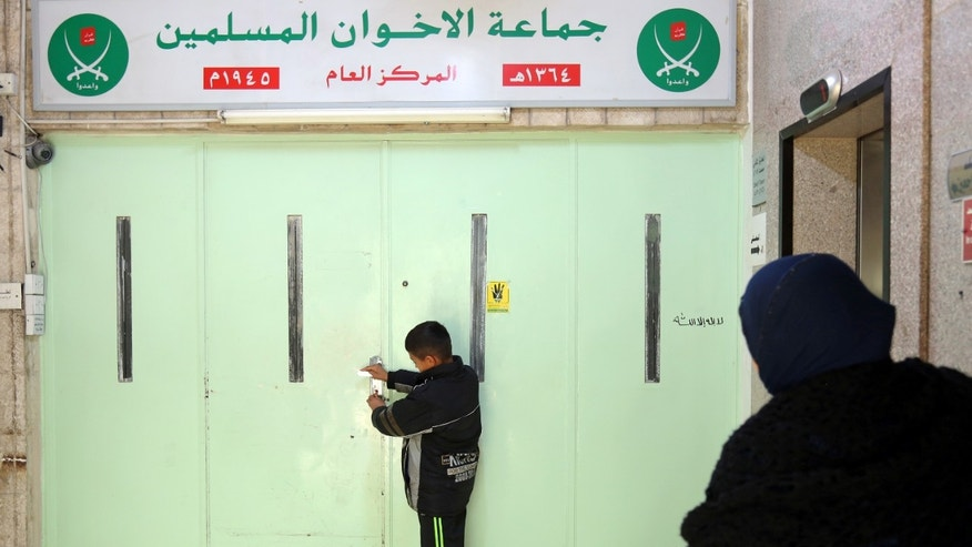 A boy stands at the main entrance of the original Muslim Brotherhood office, sealed with wax.