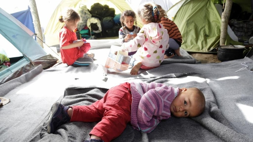 Migrant children play inside a tent at the northern Greek border point of Idomeni, Greece, Thursday, April 14, 2016. More than 12,000 people have been stuck her for more than a month amid hopes that the border would reopen.(AP Photo/Amel Emric)