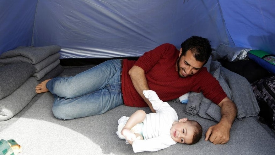 A migrant plays with his baby inside tent at the northern Greek border point of Idomeni, Greece, Thursday, April 14, 2016. More than 12,000 people have been stuck her for more than a month amid hopes that the border would reopen.(AP Photo/Amel Emric)