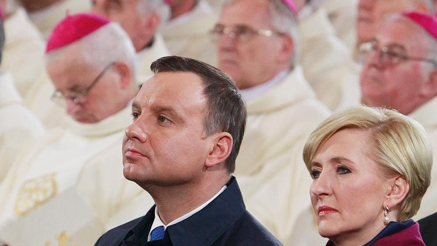 Poland's President Andrzej Duda,center, and his wife Agata Kornhauser-Duda attend a Mass as part of Poland's celebration of 1,050 years of the nation's Catholicism at the 10th-century cathedral in Gniezno, in western Poland, Thursday, 14 April 2016. Poland's bishops on Thursday opened religious and political celebrations that mark 1,050 years of Christianity in Poland with a debate on its significance for the nation.  The church and the conservative government jointly organized the three-day ceremonies that opened Thursday in the western town of Gniezno, considered to be the cradle of Poland's Catholicism. (AP Photo/Czarek Sokolowski)
