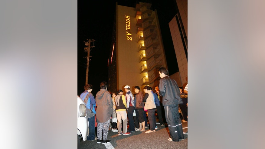 People gather outside a hotel after an earthquake in Kumamoto, southern Japan, Thursday, April 14, 2016.  A powerful earthquake with a preliminary magnitude of 6.4 has struck southern Japan. Japan's Meteorological Agency said the quake hit at 9:26 p.m. (1226 GMT) and was centered in the Kumamoto prefecture. (Kyodo News via AP) JAPAN OUT, MANDATORY CREDIT
