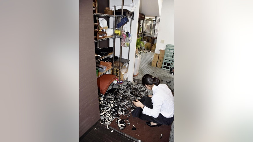 A woman collects fallen dishes at a restaurant after an earthquake in Kumamoto, southern Japan, Thursday, April 14, 2016.  A powerful earthquake with a preliminary magnitude of 6.4 has struck southern Japan. Japan's Meteorological Agency said the quake hit at 9:26 p.m. (1226 GMT) and was centered in the Kumamoto prefecture. (Kyodo News via AP) JAPAN OUT, MANDATORY CREDIT
