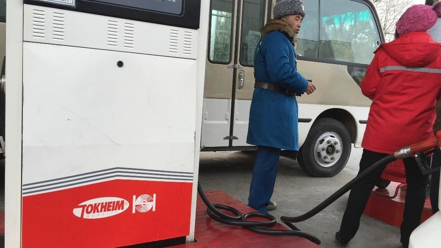 In this Feb. 22, 2016 photo, a customer talks to a gas station attendant in Pyongyang, North Korea. Gas stations have been springing up all over Pyongyang over the past few years, reflecting a major increase in traffic. But with gas prices going up, drivers in Pyongyang are starting to feel some pain at the pump, which might not be good news for the isolated country's shifting domestic economy. (AP Photo/Eric Talmadge)