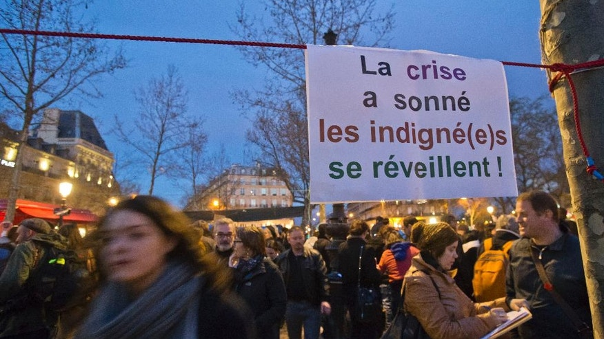 "A paper hangs which reads, ""the crisis has rung, the indignant are waking up"" as people gather on the Place de la Republique, in Paris, France, Wednesday, April 13, 2016. Thousands of protesters have been camping out, holding night-time demonstrations at a symbolic rallying point on the Place de la Republique, to express anger at a proposed labor law and social conditions in France. The social media-driven movement, called ""Nuit Debout"" or ""Rise up at Night,"" sprang from nationwide strikes and protests. (AP Photo/Michel Euler)"
