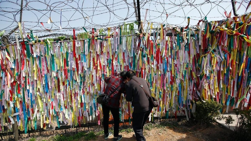 Visitors look through a wire fence decorated with ribbons with messages wishing for the reunification of the two Koreas at the Imjingak Pavilion near the border with North Korea, in Paju, in Seoul, South Korea, Friday, April 15, 2016. A North Korean launch of a missile on the birthday of its revered founder appears to have failed, South Korean and U.S. defense officials said Friday. (AP Photo/Lee Jin-man)