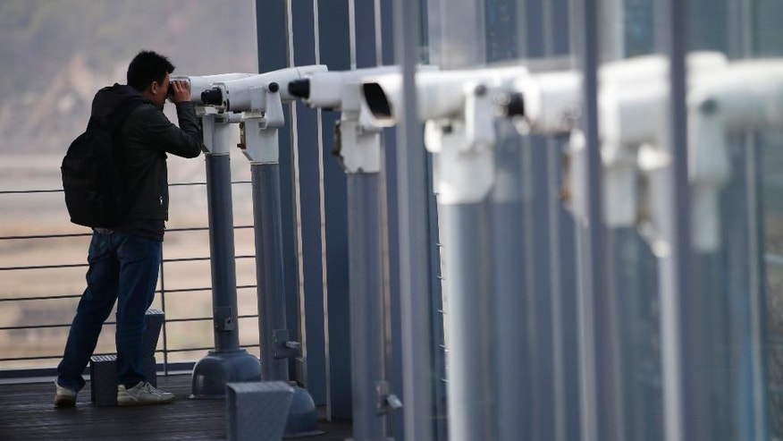 A man uses binoculars to watch the North side at the Imjingak Pavilion near the border with North Korea, in Paju, in Seoul, South Korea, Friday, April 15, 2016. A North Korean launch of a missile on the birthday of its revered founder appears to have failed, South Korean and U.S. defense officials said Friday. (AP Photo/Lee Jin-man)