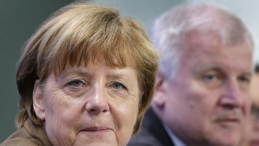 German Chancellor Angela Merkel, left, and Horst Seehofer, Chairman of the German Christian Social Union, right, attend a press conference in Berlin, Germany, Thursday, April 14, 2016 on the results of a meeting of the heads of the German government coalition. (AP Photo/Michael Sohn)