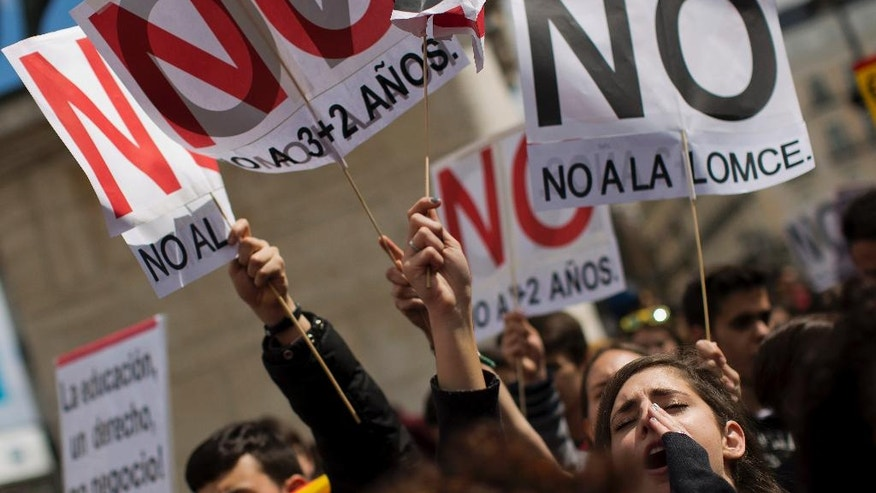 "Students shout slogans against the Spanish government during a demonstration in Madrid, Spain, Thursday, April 14, 2016. Thousands of university students opposed to increased costs for higher education programs, took part in different protests in Madrid and Barcelona. Banner on the right reads ""Not to the LOMCE (Spanish education legislation)"" (AP Photo/Emilio Morenatti)"