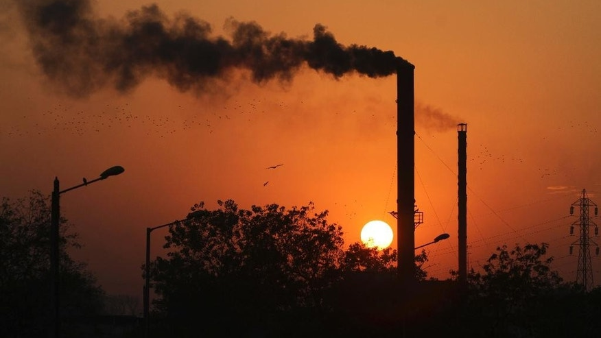 FILE - This is a Monday, Dec. 8, 2014 file photo of birds as they fly past at sun set as smoke emits from a chimney at a factory in Ahmadabad, India. The U.N.'s scientific panel on climate change will write a special report on how to limit global warming to 1.5 degrees Celsius (2.7 degrees Fahrenheit) compared with pre-industrial times. Temperatures have already risen almost 1 degree C (1.8 F) since humans started burning fossil fuels — the biggest source of greenhouse gases — on an industrial scale in the 19th century. (AP Photo/Ajit Solanki, File)