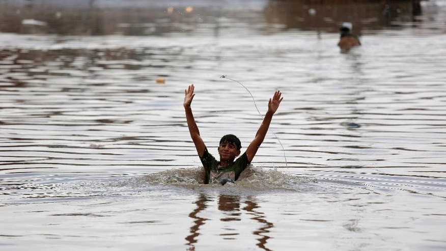 A boy swims in flood waters on a rainy day in Sanaa, Yemen, Wednesday, April 13, 2016. (AP Photo/Hani Mohammed)
