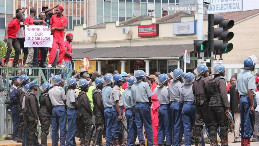 Zimbabwean police officers keep an eye on opposition party supporters as they prepare to march during a protest aimed at President Robert Mugabe in Harare, Zimbabwe, Thursday, March, 14, 2016. Morgan Tsvangirai, one of the main opposition supporters, addressed the demostrators and called on the government to take action in addressing the issues ordinary Zimbabweans are facing(AP Photo/Tsvangirayi Mukwazhi)