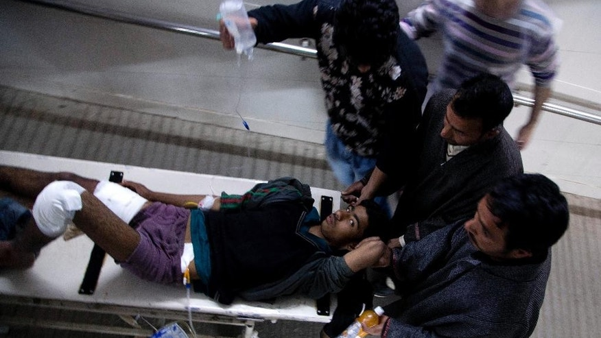 Kashmiri Muslims carry an injured protester on a stretcher at a local hospital in Srinagar, Indian controlled Kashmir, Friday, April 15, 2016. Police in Indian Kashmir say army troops have opened fire on protesters throwing rocks at a military camp in the troubled Himalayan region, killing at least one person and injuring three others. (AP Photo/Dar Yasin)