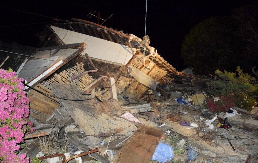 A house collapses following the earthquake in Mashiki, near Kumamoto city, southern Japan,  early Friday, April 15, 2016.  Rescuers in southern Japan are searching for trapped residents in at least two dozen collapsed houses, after a powerful earthquake struck. (Yuta Iida/Kyodo News via AP) JAPAN OUT, MANDATORY CREDIT