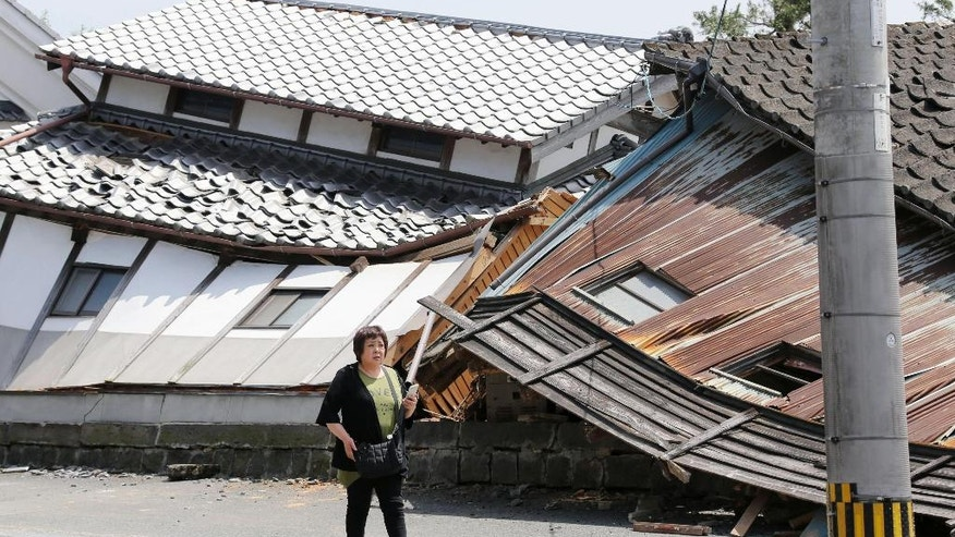 A woman walks past houses destroyed by Thursday's earthquake in Mashiki, Kumamoto prefecture, southern Japan, Friday, April 15, 2016. The powerful earthquake struck Thursday night, knocking down houses and buckling roads. (Naoya Osato/Kyodo News via AP) JAPAN OUT, MANDATORY CREDIT