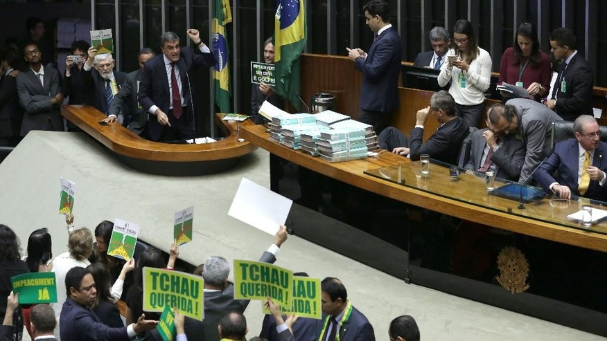 "Brazil's Attorney General Jose Eduardo Cardozo, top left, presents the defense of Brazil's President Dilma Rousseff in the Chamber of Deputies, as opposition lawmakers hold signs that read in Portuguese ""Goodbye dear"" and ""Impeachment now"" in Brasilia, Brazil, Friday, April 15, 2016.  The lower chamber of Brazil's Congress began the debate on whether to impeach Rousseff, a question that underscores deep polarization in Latin America's largest country and most powerful economy. (AP Photo/Eraldo Peres)"