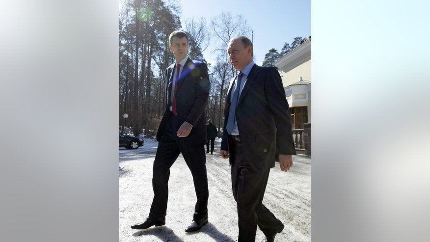 "FILE In this Friday, April 1, 2011 file photo then Russian Prime Minister Vladimir Putin, right, walks with Russian billionaire Mikhail Prokhorov to have a look at the new Russian-designed hybrid cars called ""Yo"" at the Gorki residence outside Moscow. Russia's main domestic security agency said Friday April 15, 2016, its agents have searched the offices of a company controlled by billionaire Mikhail Prokhorov, the owner of Brooklyn Nets.  (Alexei Nikolsky/Sputnik, Kremlin Pool Photo via AP, File)"