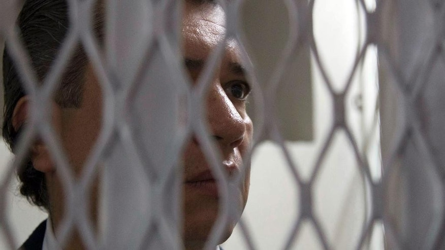 FILE - In this July 9, 2015, Gustavo Martinez, son-in-law of Guatemala's President Otto Perez Molina, stands inside a court holding cell in Guatemala City. Martinez, who had served until April 2015, as the president's private secretary, was arrested based on investigations by the federal prosecutors' office and the U.N. International Commission Against Impunity in Guatemala for alleged influence trafficking. Martinez was eventually freed, but then arrested again on April 15, 2016, for alleged involvement in irregularities also involving his father-in-law. (AP Photo/Luis Soto, File)