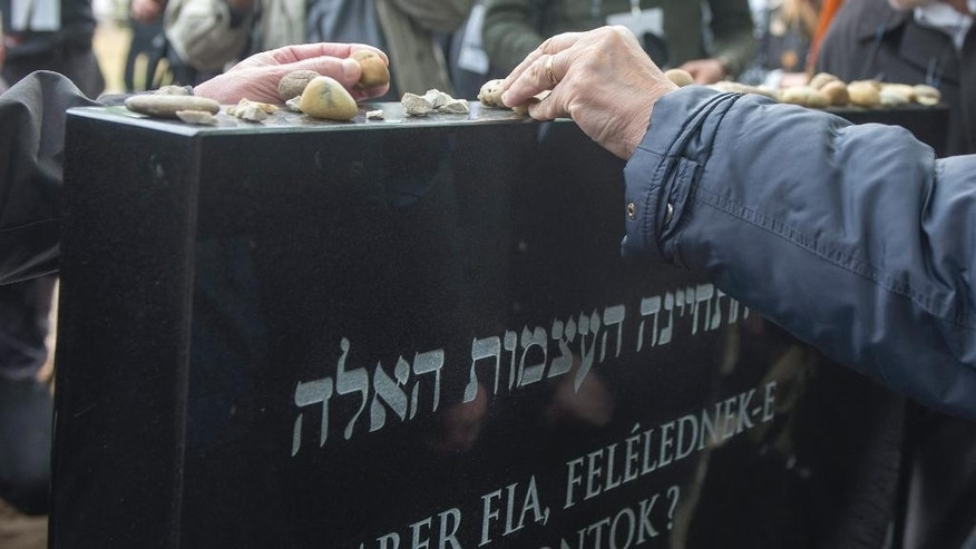 Attendees place pebbles atop a memorial tomb with the words 'Son of Man, shall these bones revive?' engraved on it during the burial service of the remains of Jewish people found in River Danube in the Kozma Street Jewish Cemetery in Budapest, Hungary, Friday, April 15, 2016. Human remains found in 2011, including many believed to be of Jews shot on the banks of the Danube River near the end of World War II, were buried Friday in a Jewish cemetery in Budapest. Two wooden caskets containing hundreds of bone fragments were laid to rest according to Jewish customs in a ceremony attended by Christian clergy and government officials.  (Tibor Illyes/MTI via AP)