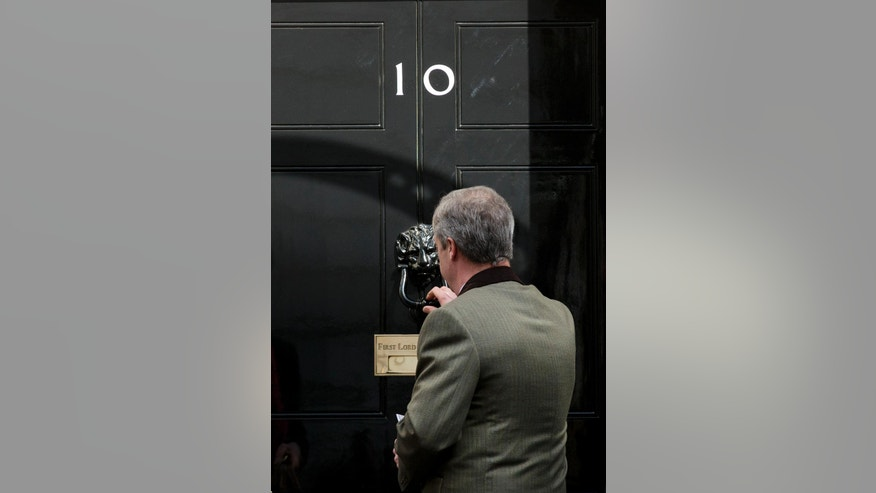 Nigel Farage, the leader of the UK Independence Party, knocks on the door of 10 Downing Street in London, as he returns and rejects a government mailshot leaflet stating their reasons for the UK to stay in the EU, Friday, April 15, 2016. Britain is to hold a referendum on their EU membership on June 23. (AP Photo/Matt Dunham)