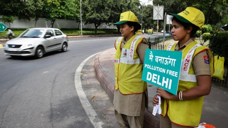 Volunteers remind commuters the reason for restriction placed on vehicle movement in New Delhi, India, Friday, April 15, 2016. The New Delhi government has begun a second round of a two-week car restriction whereby private cars will be allowed on the streets on alternate days from Friday until April 30 based on even or odd license plate numbers, to reduce air pollution that has made the Indian capital the world's most polluted city. (AP Photo/Saurabh Das)