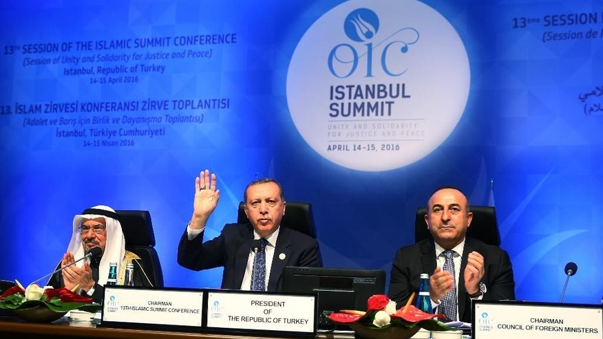 Turkey's President Recep Tayyip Erdogan, center, addresses the leaders and representatives of the Islamic countries during the second day of the 13th Organization of Islamic Cooperation, OIC, Summit in Istanbul, Friday, April 15, 2016.  Muslim nations have agreed to establish a joint body based in Istanbul to fight terrorism. The OIC Secretary-General Iyad Ameen Madani, left, and Turkish Foreign Minister Mevlut Cavusoglu applaud.(Anadolu Agency, Pool via AP)