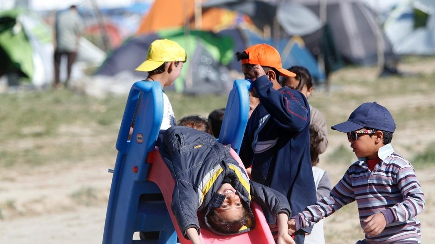Migrant children play at the northern Greek border point of Idomeni, Greece, Friday, April 15, 2016. More than 12,000 people have been stuck near Idomeni for more than a month amid hopes that the border would reopen.(AP Photo/Amel Emric)