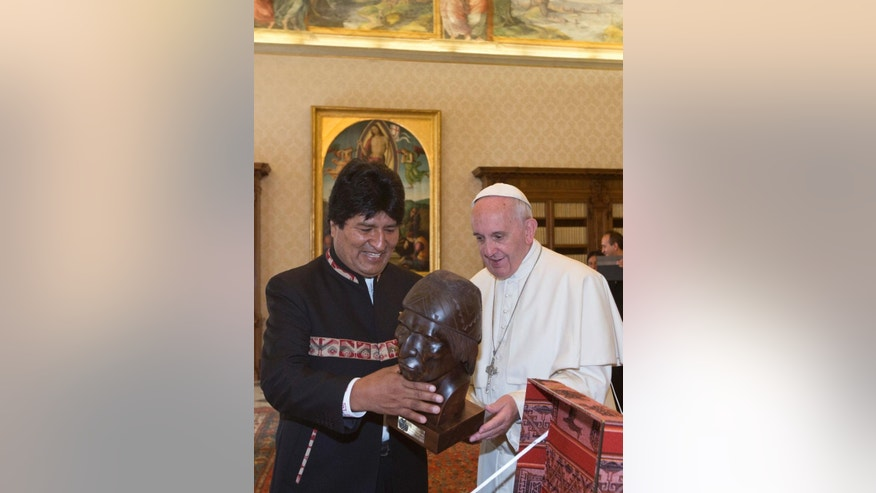 Bolivia's President Evo Morales, left, presents Pope Francis with a handcrafted bust of Bolivia's indigenous leader Tupac Katari on the occasion of their private meeting in the Apostolic Palace at the Vatican, Friday, April 15, 2016. (AP Photo/Alessandra Tarantino, pool)