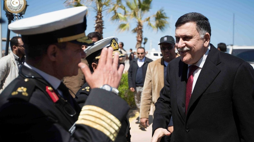 This image released by the Media office of the Unity Government (GNA MEDIA) on Wednesday, March 30, 2016 shows Fayez Serraj, right, a U.N.-brokered Libyan unity government on arrival in Tripoli, Libya.