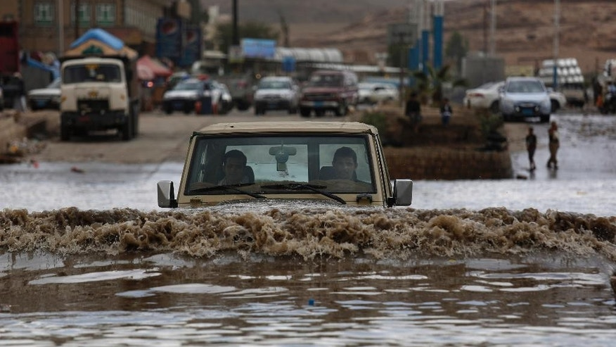 A motorist drives in floodwaters after a heavy rain in Sanaa, Yemen, Wednesday, April 13, 2016. (AP Photo/Hani Mohammed)