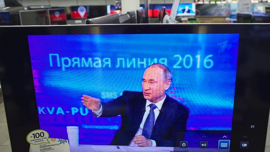 "The marathon call-in TV show with Russian President Vladimir Putin is seen on TV screens in an electronic store in Moscow, Russia, on Thursday, April 14, 2016. Russian President Vladimir Putin says the United States must abandon its ""imperial ambitions"" and treat Russia as an equal partner. (AP Photo/Ivan Sekretarev)"
