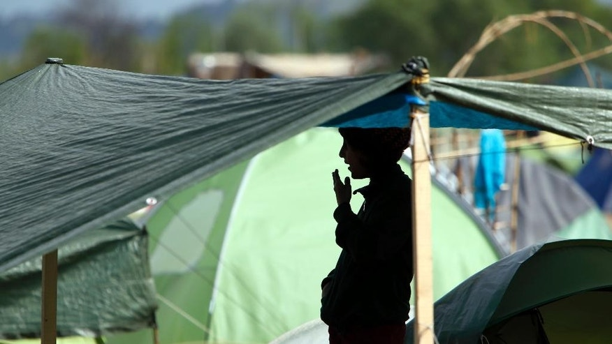 A migrant stands inside a tent at the northern Greek border point of Idomeni, Greece, Thursday, April 14, 2016. More than 12,000 people have been stuck her for more than a month amid hopes that the border would reopen.(AP Photo/Amel Emric)