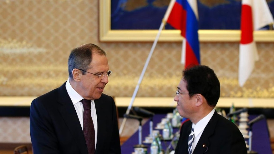 Russia's Foreign Minister Sergey Lavrov, left, and his Japanese counterpart Fumio Kishida, right, shake hands at the foreign ministry's Iikura guest house in Tokyo, Japan, Friday, April 15, 2016. (Toru Hanai/Pool Photo via AP)