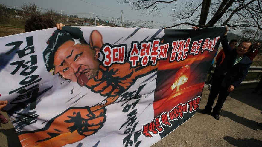 "South Korean conservative activists hold an anti-North Korea banner with a caricature of North Korean leader Kim Jong Un as police block the conservative activists attempting to release balloons with leaflets during a rally at the border city with North Korea, in Paju, South Korea, Friday, April 15, 2016. A North Korean launch of a missile on the birthday of its revered founder appears to have failed, South Korean and U.S. defense officials said Friday. The banners read ""Overthrow, three generation dictatorship Kim Jong Un."" (AP Photo/Lee Jin-man)"
