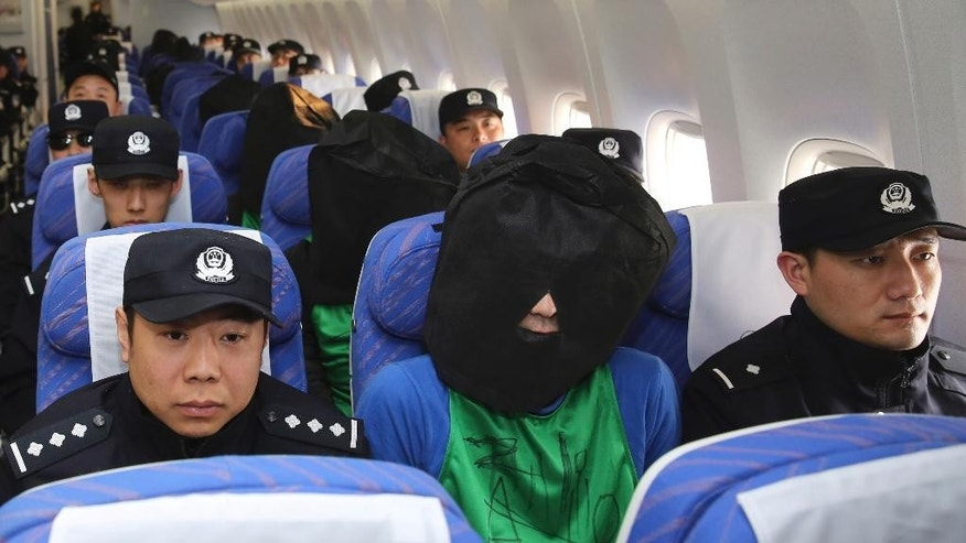 FILE - In this April 13, 2016, file photo released by Xinhua News Agency, Chinese and Taiwanese suspects involved in wire fraud, center, sit in a plane as they arrive at the Beijing Capital International Airport in Beijing, China. Taiwan on Friday was trying to prevent Malaysia from deporting 52 Taiwanese criminal suspects to China amid an ongoing battle over jurisdiction involving the self-ruled island. (Yin Gang/Xinhua News Agency via AP, File) NO SALES
