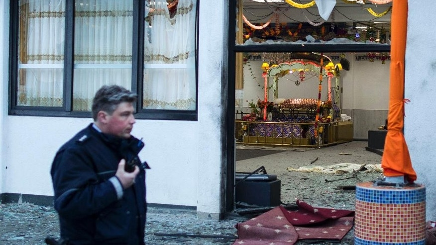 A police officers stand passes by a Sikh temple after three people have been injured in an apparently deliberate explosion Saturday evening, April 16, 2016 in the western German city of Essen.  A spokesman for Essen police told The Associated Press that a masked person is reported to have fled the scene shortly after the blast. (Marcel Kusch/dpa via AP)