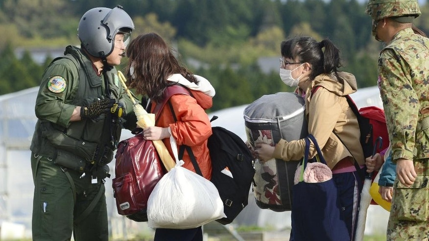 College students with their belongings wait for the arrival of a helicopter of the Japan Self-Defense Forces to be transferred to safer place in Minamiaso village, Kumamoto prefecture, Japan, Saturday, April 16, 2016. The powerful earthquake struck southwestern Japan early Saturday, barely 24 hours after a smaller quake hit the same region. (Hiroko Harima/Kyodo News via AP) JAPAN OUT, MANDATORY CREDIT