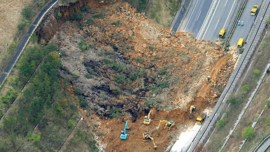 Heavy machinery works recovery efforts of Oita Expressway damaged by a landslide following an earthquake in Yufu, Oita prefecture, Japan, Saturday, April 16, 2016. Powerful earthquakes shook southwestern Japan, trapping many others beneath flattened homes and sending thousands of residents to seek refuge in gymnasiums and hotel lobbies. (Sadayuki Goto/Kyodo News via AP) JAPAN OUT, MANDATORY CREDIT