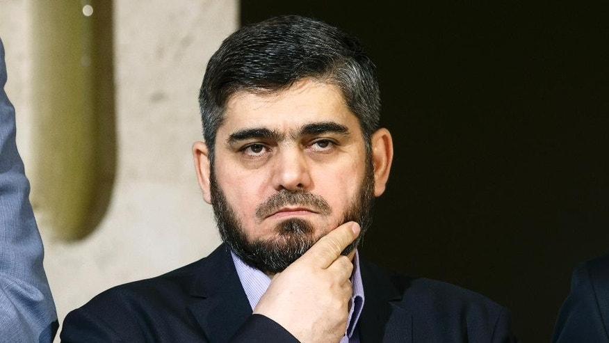 Mohammed Alloush, chief negotiator for the main Syrian opposition body and rebel group Army of Islam, listens during a briefing after a round of negotiation between the Syrian opposition and the UN Special Envoy of the Secretary-General for Syria Staffan de Mistura at the European headquarters of the United Nations in Geneva, Switzerland, Friday, April 15, 2016. (Salvatore Di Nolfi/Keystone via AP)