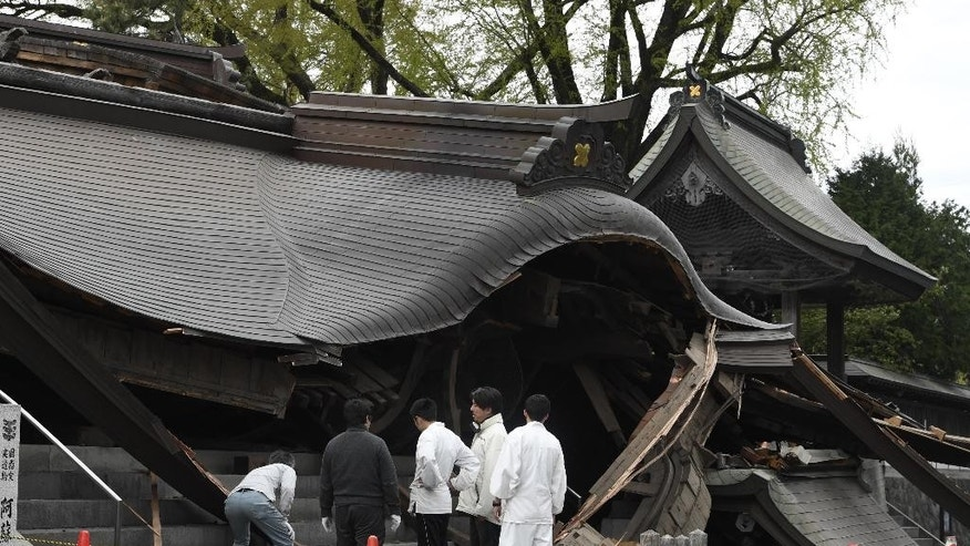 Staff of the historic Aso Shrine examine its gate collapsed by n earthquake in Aso, Kumamoto prefecture, Japan Saturday, April 16, 2016. Powerful earthquakes a day apart shook southwestern Japan, trapping many others beneath flattened homes and sending thousands of residents to seek refuge in gymnasiums and hotel lobbies. (Yohei Fukai/Kyodo News via AP) JAPAN OUT, MANDATORY CREDIT