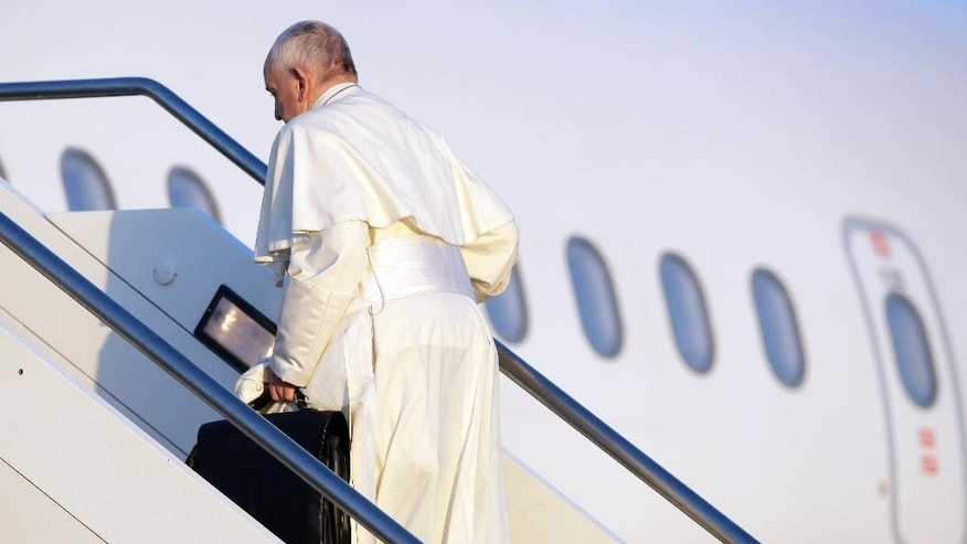 Pope Francis boards an airplane at Rome's Fiumicino airport, Saturday, April 16, 2016, on his way to the Greek island of Lesbos, The Pontiff will visit the island Saturday joined by Ecumenical Patriarch Bartholomew and the head of the Orthodox Church of Greece, Athens Archbishop Ieronymos II, a mission human rights groups hope will highlight the plight of refugees who fled their war-ravaged homes only to be denied entry to Europe. (AP Photo/Gregorio Borgia)