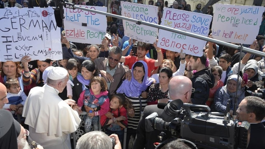 Pope Francis meets migrants at the Moria camp on the Greek island of Lesbos, Saturday, April 16, 2016. Pope Francis' Saturday visit to the Greek island of Lesbos, whose shores have seen the arrival of hundreds of thousands of people making their way toward Europe, might have been brief but it was highly emotional, with some of the refugees and migrants he met breaking down and weeping at his feet. (L'Osservatore Romano/Pool photo via AP)
