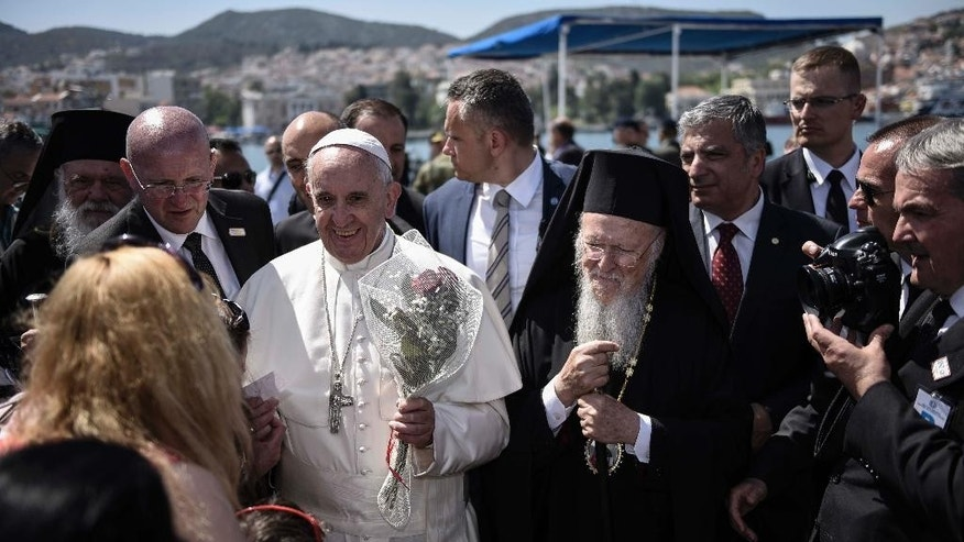 "In this photo released by Greek Prime Minister's office on Saturday, April 16, 2016, Pope Francis, left, is escorted by Ecumenical Patriarch Bartholomew I, during a visit on the Greek island of Lesbos. Pope Francis implored Europe on Saturday to respond to the migrant crisis on its shores ""in a way that is worthy of our common humanity,"" during an emotional and provocative trip to Greece.  (Andrea Bonetti/Greek Prime Minister's Office via AP)"